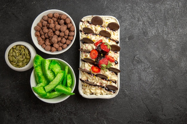 Bovenaanzicht heerlijk dessert met chocoladekoekjes en aardbeien op een donkere achtergrond, notenkoekje, zoete fruitkoekjes, suiker