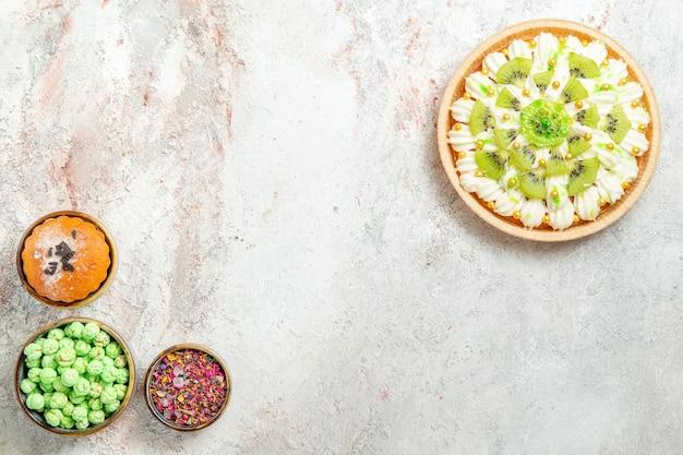 Bovenaanzicht heerlijk dessert met gesneden kiwi's en snoepjes op witte achtergrond biscuit crème fruit dessert snoep cake