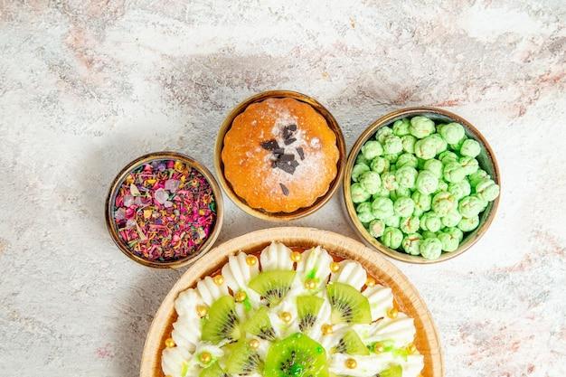 Bovenaanzicht heerlijk dessert met gesneden kiwi's en snoepjes op witte achtergrond dessert crème vruchten cake snoep