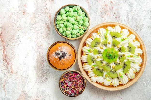 Bovenaanzicht heerlijk dessert met gesneden kiwi's en snoepjes op witte achtergrond dessertcrème fruitcake snoep
