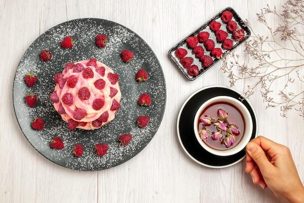 Bovenaanzicht heerlijk fruitcake crème dessert met frambozen en kopje thee op witte achtergrond zoete cream tea dessert biscuit cake pie