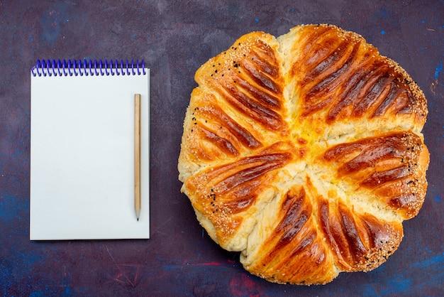 Bovenaanzicht heerlijk gebak gebakken broodje gevormd gebak met blocnote op de donkere achtergrond.