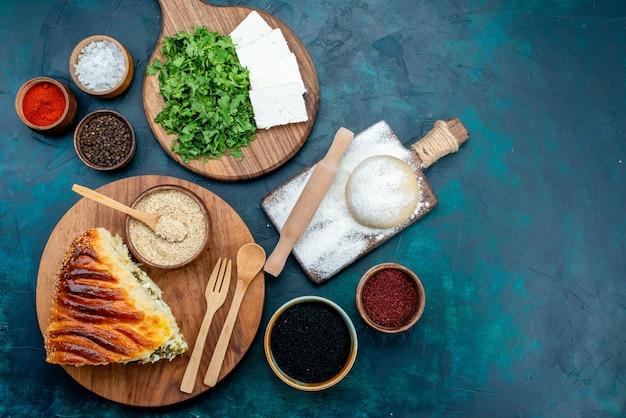 Bovenaanzicht heerlijk gebakken gebak gesneden met greens binnen, samen met verse witte kaas en greens op donkere achtergrond.