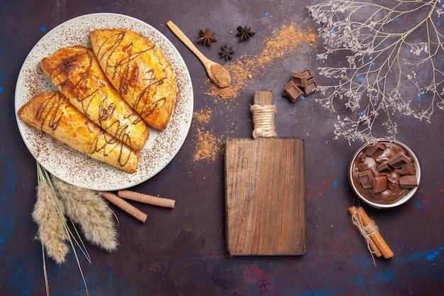 Bovenaanzicht heerlijk gebakken gebak met chocoladedessert op donkere ruimte