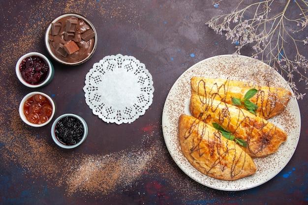 Bovenaanzicht heerlijk gebakken gebak met jam op donkere ruimte