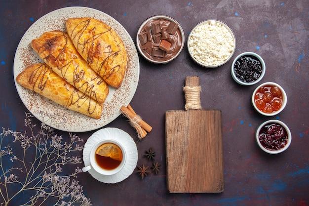 Bovenaanzicht heerlijk gebakken gebak met kopje thee en jam op donker bureau