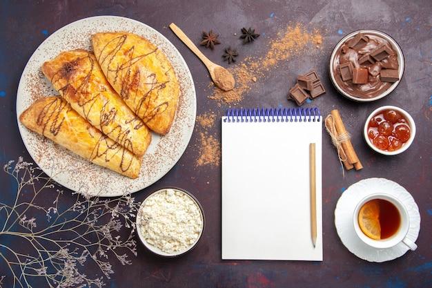 Bovenaanzicht heerlijk gebakken gebak met kopje thee en kwark op donkere ruimte