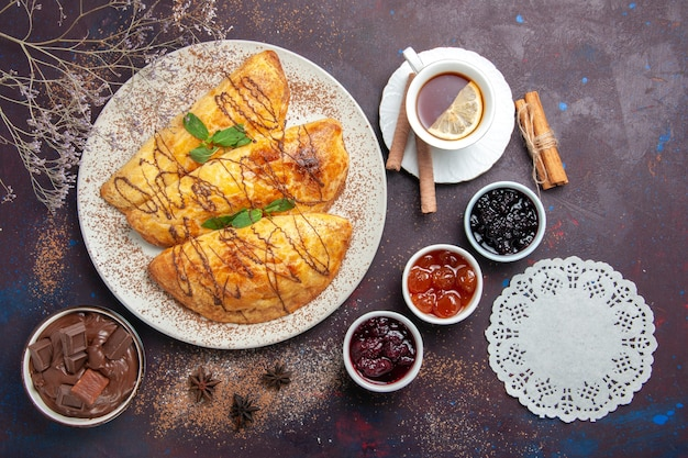 Bovenaanzicht heerlijk gebakken gebak met kopje thee jam op donkere ruimte