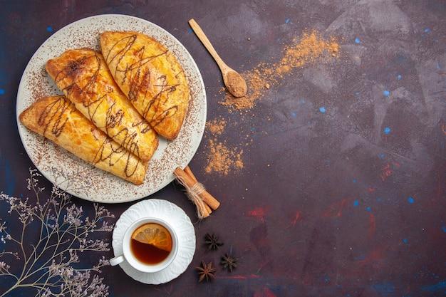 Bovenaanzicht heerlijk gebakken gebak met kopje thee op de donkere ruimte