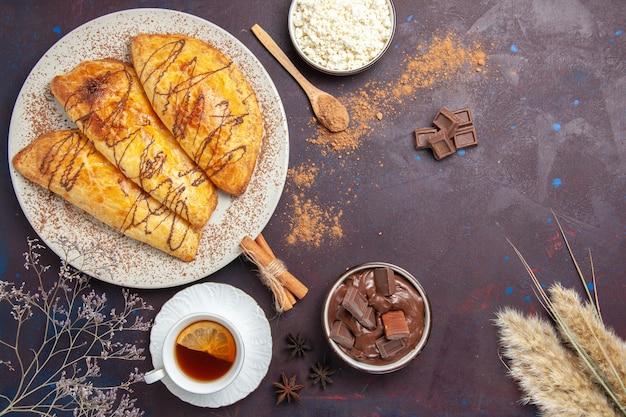 Bovenaanzicht heerlijk gebakken gebak met kwark en thee op de donkere ruimte