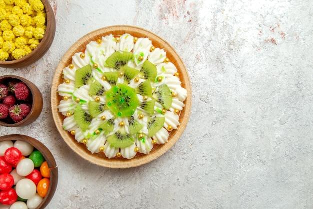 Bovenaanzicht heerlijk kiwi-dessert met snoepjes op lichte witte achtergrond dessert cake crème fruit tropisch