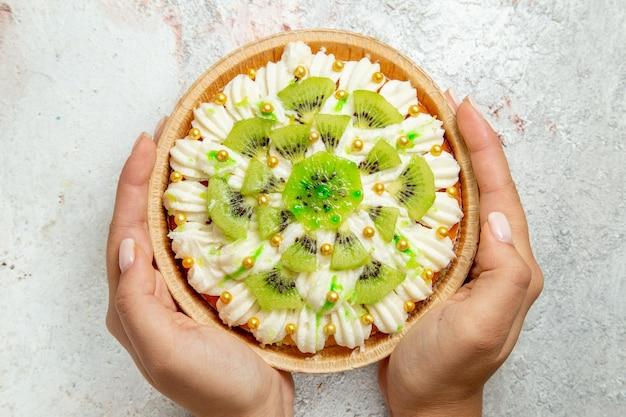Bovenaanzicht heerlijk kiwi-dessert met witte room en gesneden kiwi's op witte achtergrond dessert fruit snoep crème taart
