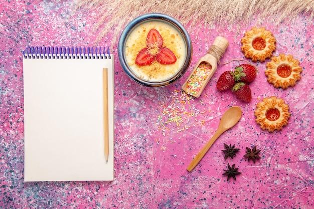 Bovenaanzicht heerlijk romig dessert met rode gesneden aardbeien blocnote en kleine koekjes op lichtroze achtergrond dessertijs bessen crème zoet fruit