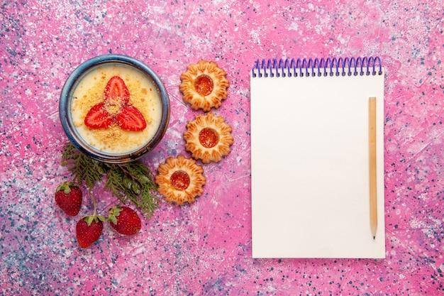 Bovenaanzicht heerlijk romig dessert met rode gesneden aardbeien en koekjes op de lichtroze achtergrond dessertijs kleur zoet ijs