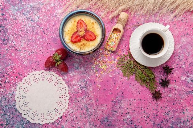 Bovenaanzicht heerlijk romig dessert met rode gesneden aardbeien en kopje thee op de lichtroze achtergrond dessertijs bessen crème zoet fruit