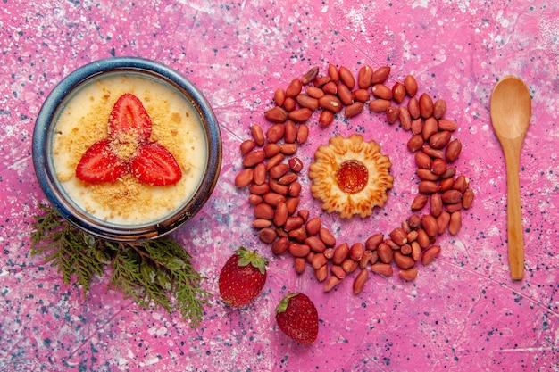 Bovenaanzicht heerlijk romig dessert met rode gesneden aardbeien en pinda's op de lichtroze achtergrond dessertijs kleur zoet fruit bes