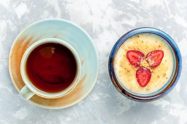 Bovenaanzicht heerlijk romig dessert met verse aardbeien en thee op lichte witte achtergrond dessertijs zoete fruitsmaak