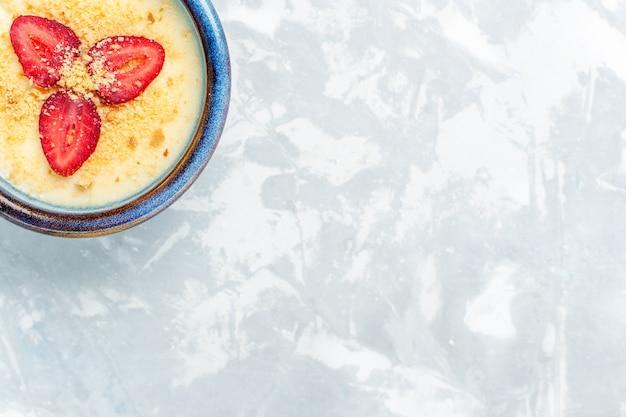 Bovenaanzicht heerlijk romig dessert met verse aardbeien op lichte witte bureau dessertijs zoete fruitsmaak