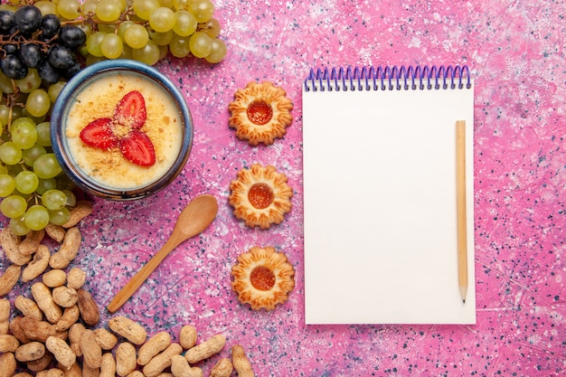 Bovenaanzicht heerlijk romig dessert met verse druiven en pinda's op lichtroze achtergrond dessert-ijs bessen crème zoet fruit
