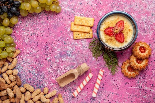 Bovenaanzicht heerlijk romig dessert met verse druiven, koekjes, crackers en pinda's op lichtroze bureau dessertijs bessen room zoet fruit