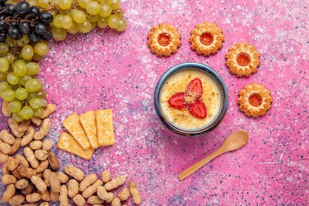 Bovenaanzicht heerlijk romig dessert met verse druiven, koekjes, crackers en pinda's op lichtroze oppervlak dessertijs bessen crème zoet fruit