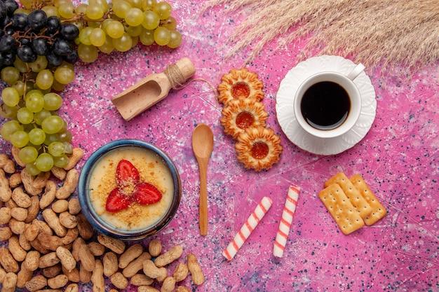 Bovenaanzicht heerlijk romig dessert met verse druivenkoekjes en pinda's op het lichtroze oppervlak dessertijs bessen crème zoet fruit