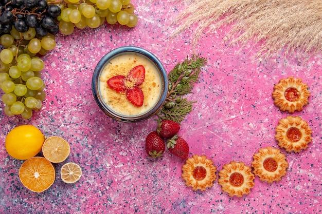 Bovenaanzicht heerlijk romig dessert met verse groene druiven en koekjes op de licht roze achtergrond dessert-ijs bessen crème zoet fruit