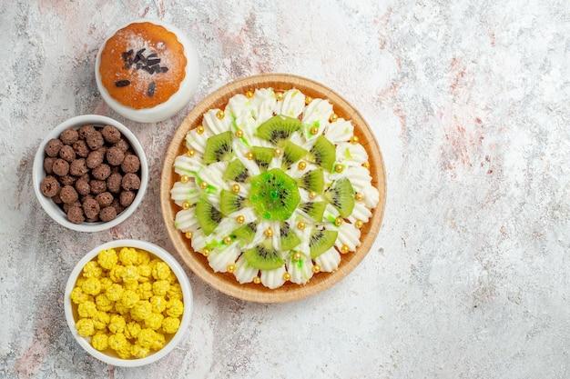 Bovenaanzicht heerlijk roomdessert met witte room en gesneden kiwi's op wit bureau candy biscuit cream cake dessert