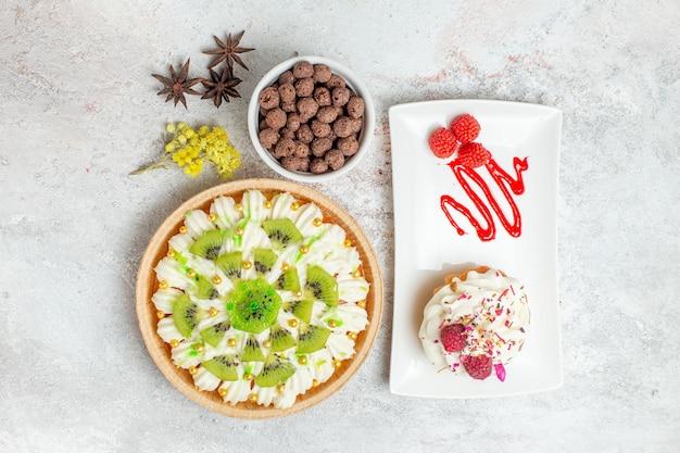 Bovenaanzicht heerlijk roomdessert met witte room en gesneden kiwi's op witte bureaukleur candy biscuit cream dessert