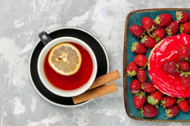 Bovenaanzicht heerlijk uitziende cake kleine taart met kopje thee en verse aardbeien op licht wit oppervlak cake koekje koekje room suiker zoet
