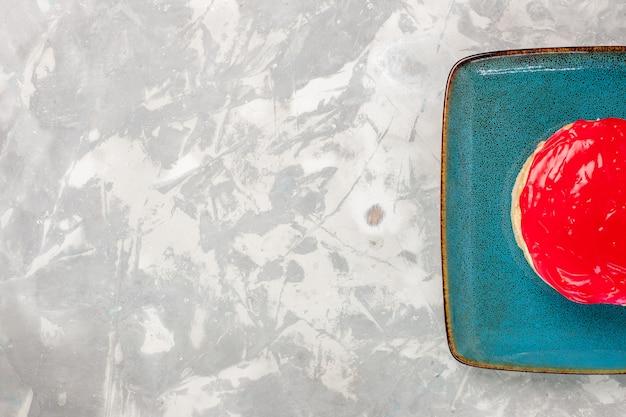 Bovenaanzicht heerlijk uitziende cake kleine taart met rode room op het witte bureau cake koekje bak room suiker zoet