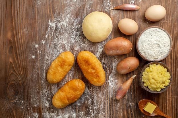 Bovenaanzicht heerlijke aardappel hotcakes met ingrediënten op bruin houten bureau cake pie hotcake bakoven
