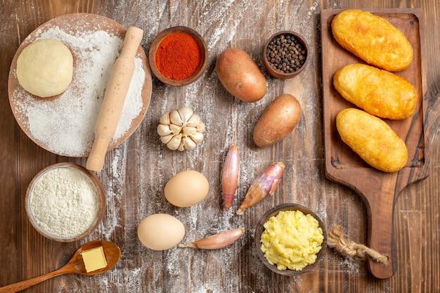 Bovenaanzicht heerlijke aardappel hotcakes met kruiden en bloem op houten bureau bak cake peper deeg kleur