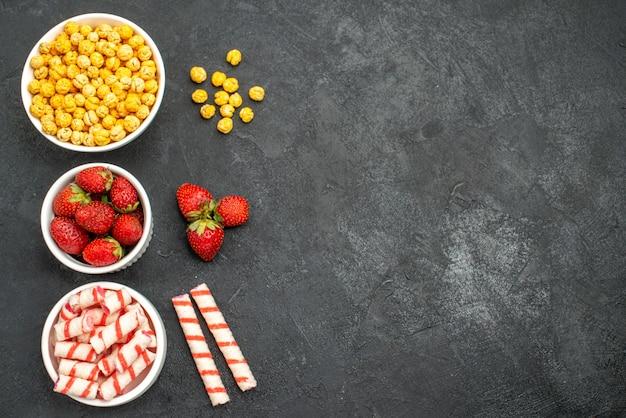 Bovenaanzicht heerlijke aardbeien met snoepjes op een zwarte achtergrond met vrije ruimte