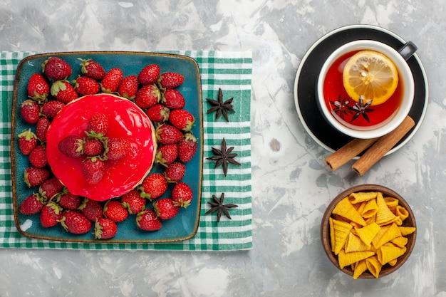 Bovenaanzicht heerlijke aardbeientaart beetje met verse aardbeien en kopje thee op lichtwitte ondergrond cake koekje bessen suiker zoet koekje
