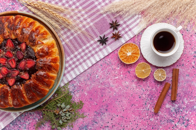 Bovenaanzicht heerlijke aardbeientaart fruitige cake met kopje thee op de roze