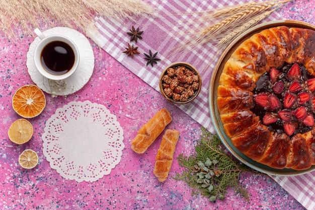 Bovenaanzicht heerlijke aardbeientaart fruitige cake met kopje thee op lichtroze