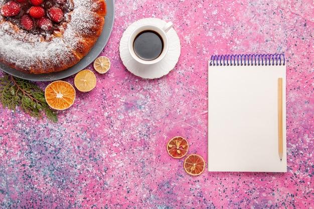 Bovenaanzicht heerlijke aardbeientaart gebakken met suikerpoeder en thee op de licht roze achtergrond cake zoete suiker biscuit koekjes taart