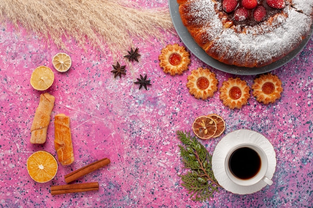 Bovenaanzicht heerlijke aardbeientaart met koekjes bagels en kopje thee op roze achtergrond cake zoete suiker koekjes taart