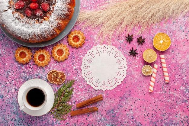Bovenaanzicht heerlijke aardbeientaart met koekjes en kopje thee op de lichtroze achtergrond taart zoete suiker koekjes taart