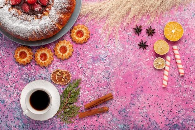 Bovenaanzicht heerlijke aardbeientaart met koekjes en kopje thee op de roze achtergrond taart zoete suiker koekjes taart