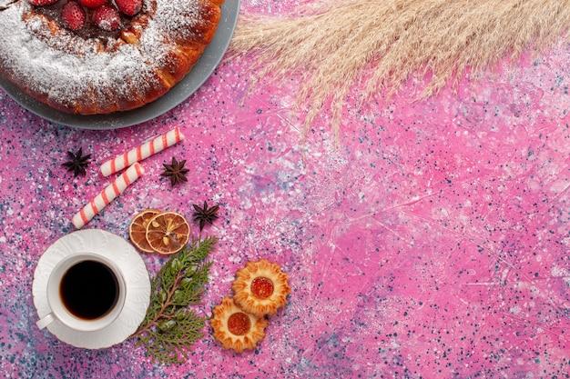 Bovenaanzicht heerlijke aardbeientaart met koekjes en kopje thee op roze bureau cake zoete suiker koekjes taart