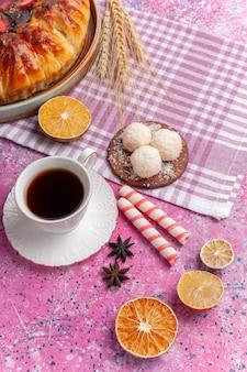Bovenaanzicht heerlijke aardbeientaart met kopje thee op een helderroze