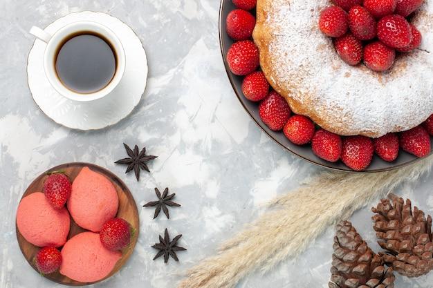 Bovenaanzicht heerlijke aardbeientaart met kopje thee op lichte vloer