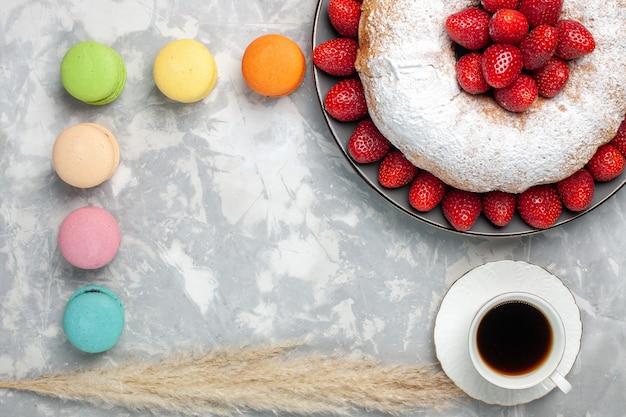 Bovenaanzicht heerlijke aardbeientaart met thee en macarons op wit
