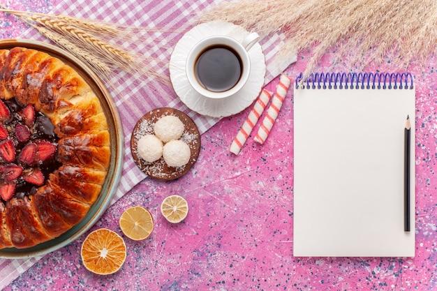Bovenaanzicht heerlijke aardbeientaart ronde gevormde fruitige cake op een roze