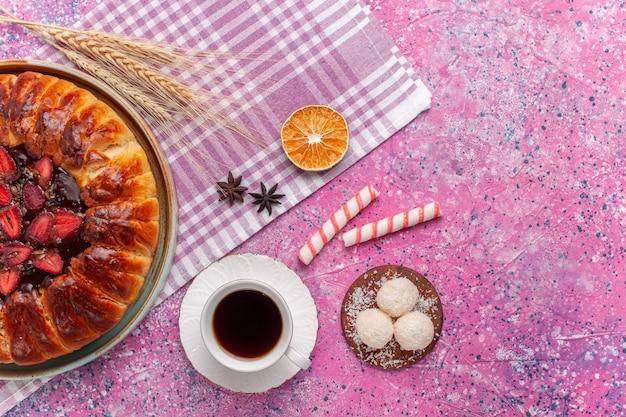Bovenaanzicht heerlijke aardbeientaart ronde gevormde fruitige cake op helder roze