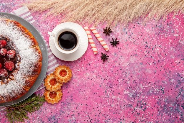 Bovenaanzicht heerlijke aardbeientaart suiker gepoederd met koekjes en thee op lichtroze achtergrond cake zoete koekje koekjesthee