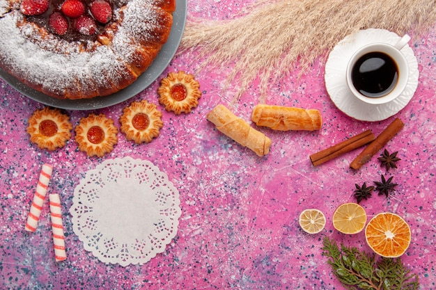 Bovenaanzicht heerlijke aardbeientaart suiker poedertaart met koekjes bagels en kopje thee op roze achtergrond cake zoete suiker koekjes taart