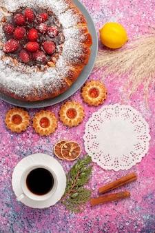 Bovenaanzicht heerlijke aardbeientaart suiker poedertaart met koekjes citroen en kopje thee op roze oppervlak cake zoete suiker koekjes taart